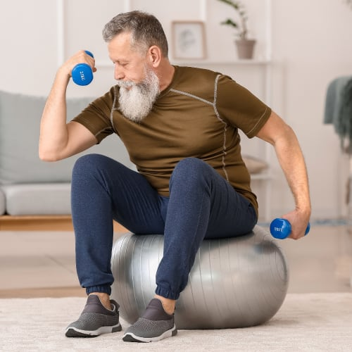 active senior man exercising at home with balance ball and hand dumbbells