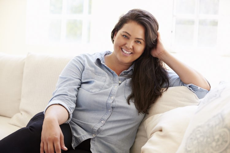 attractive, overweight, hispanic woman sitting on couch smiling
