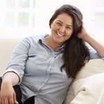 attractive, overweight hispanic woman smiling on couch