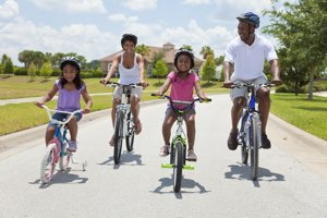 attractive young black family riding bicycles together