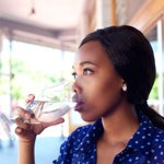black woman drinking a glass of water on porch