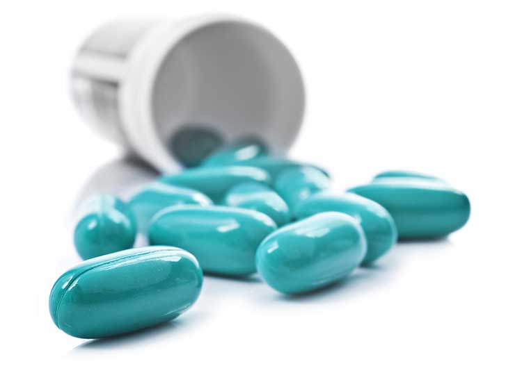 bottle of blue pills on white background