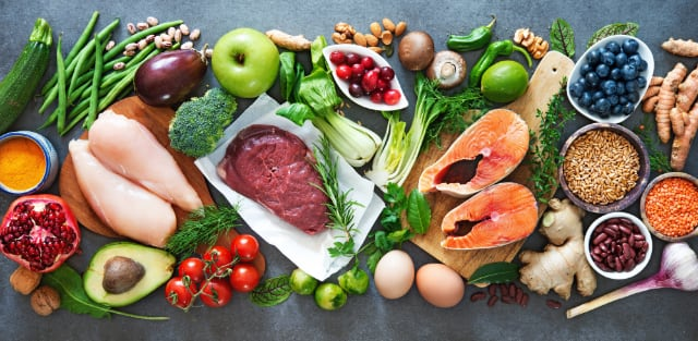 assortment of superfoods including salmon, avacado, berries, nuts, apples and others