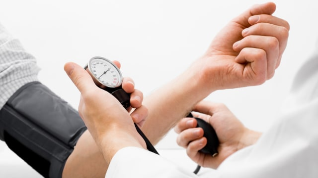 healthcare provider taking a patient's blood pressure in an office visit