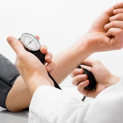 healthcare provider measuring a patient's blood pressure