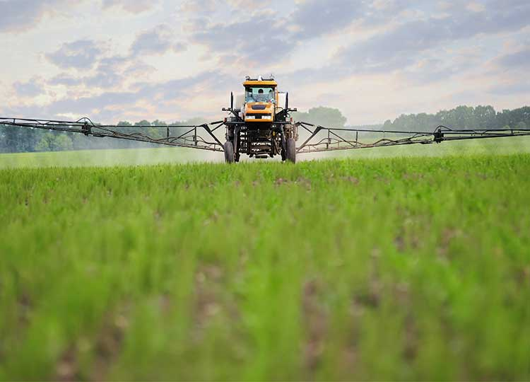 farmer sprays pesticides on crops