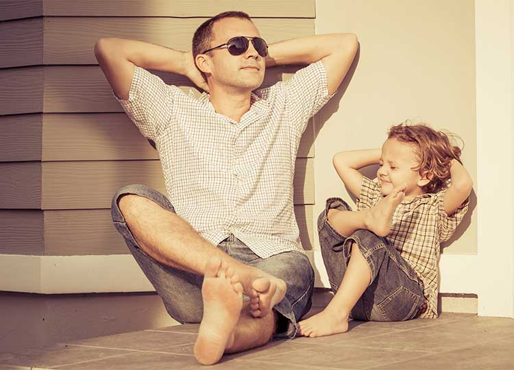 Father and son relax on front porch