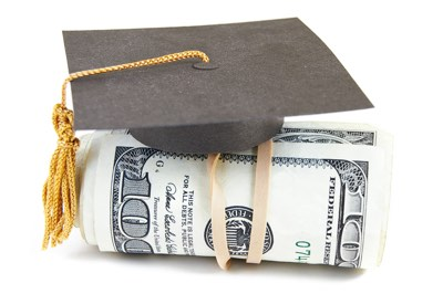 graduation cap sitting on top of a stack of 100 dollar bills
