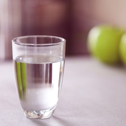 glass of water with green apple