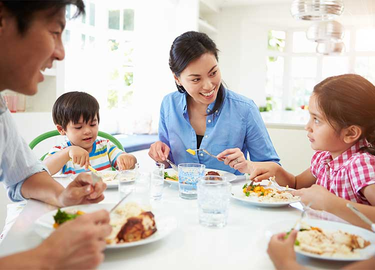 Happy young asian family eating a healthy meal together at table.