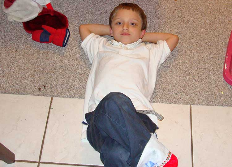 Little boy laying on carpet smiling up at camera