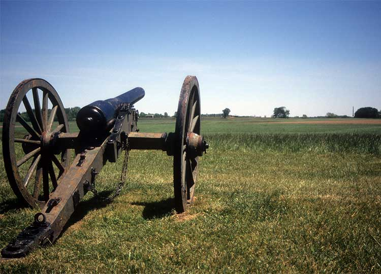 old cannon aimed out over a field