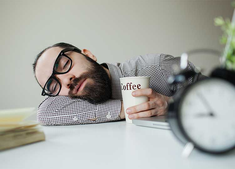 Bearded Man Sleeping at Desk with Coffee At 9 AM
