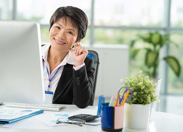 Middle-aged Asian Woman Sitting at Desk