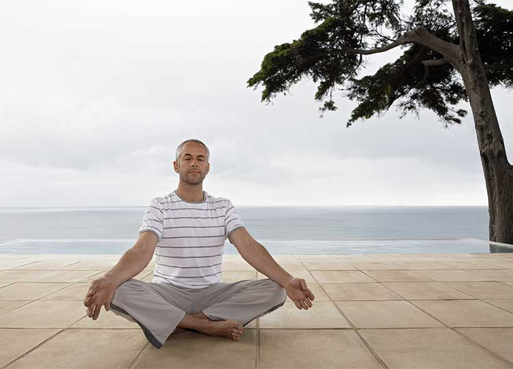 Middle-aged Man Meditating on Beach