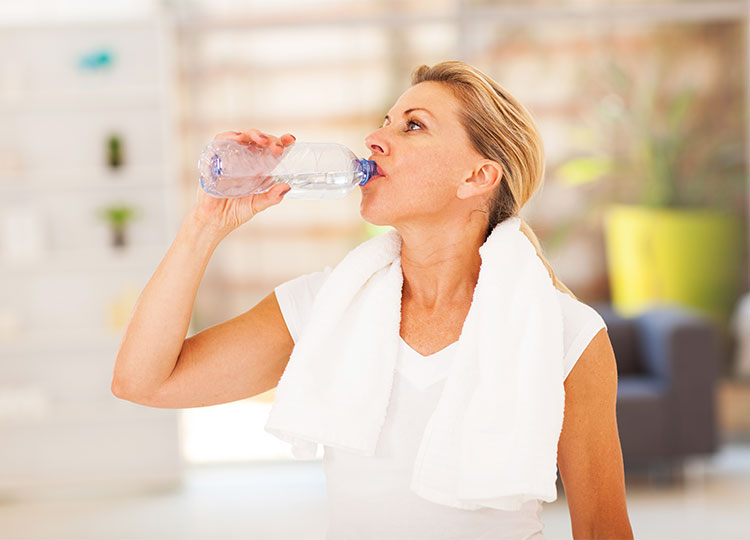 a woman drinks water after exercising