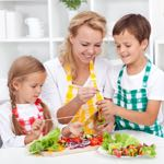 mother cooking healthy food with young son and daughter