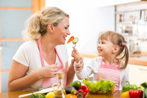 mother and daughter in kitchen enjoying a healthy salad together