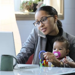 mother working at home on computer with baby