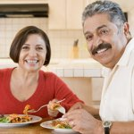older hispanic couple enjoying home-cooked meal together