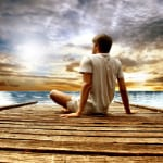perspective of man gazing from pier at water and sky