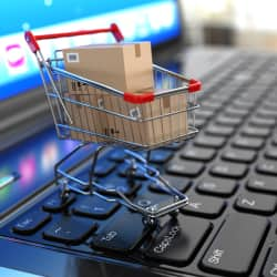 shopping cart with cardboard boxes sitting on a computer keyboard for e-commerce shopping
