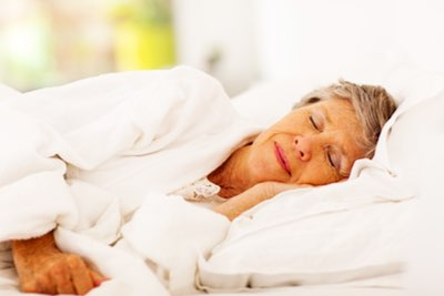 Elderly woman sleeping comfortably in bed.
