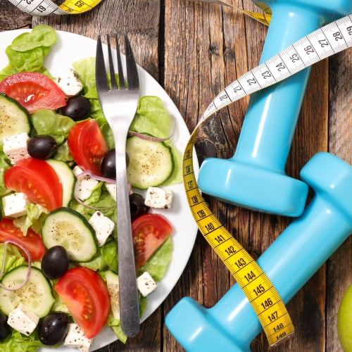 things related to weight loss including healthy foods , exercise equipment and a journal