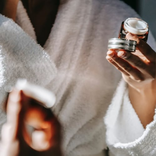 woman in bathrobe applying skin care product to her face