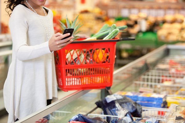 woman grocery shopping for gluten free and dairy free foods using smartphone