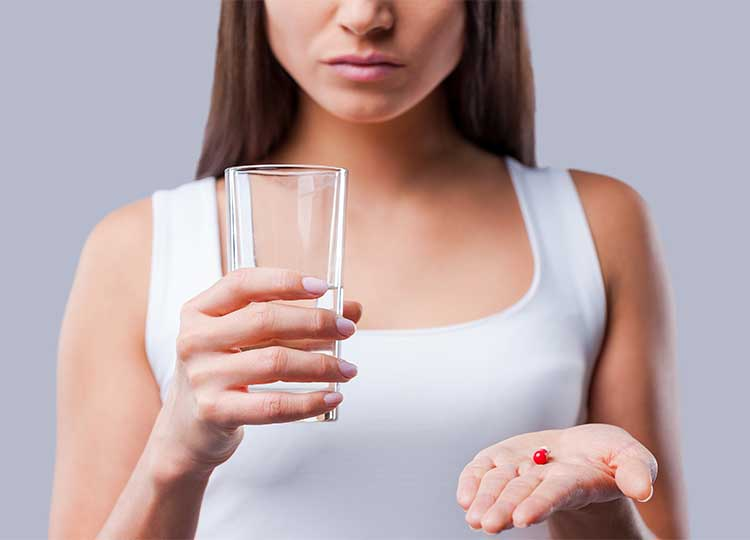 Unhappy Woman holding pill with water