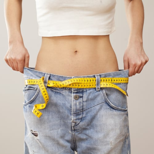 a woman showing off her loose fitting jeans after weight loss