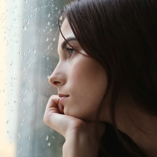 younger attractive woman staring sadly out a window looking at the rain