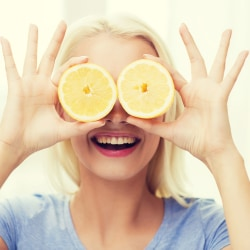 blond woman smiling with lemon halves over her eyes