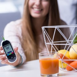woman holding a digital blood sugar monitor in her hand on table with healthy foods