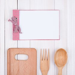 Healthy Living Whole Foods Cookbook displaying wooden cooking utensils and recipe notepad.