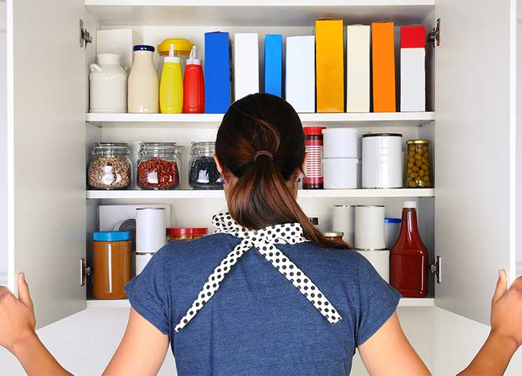 Young Caucasian Woman Looking into Well Stocked Cupboard