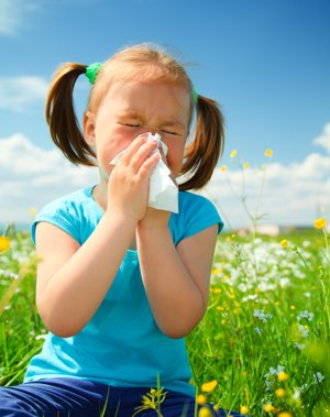 young girl sneezing into a kleenex in a field full of flowers