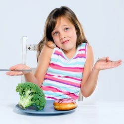 young girl choosing between eating broccoli or a donut