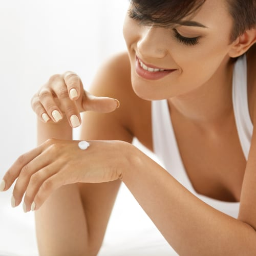 young woman applying body lotion to the back of her hand